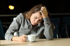 El quejarse adolescente triste en una cafetería en la noche Fotos de archivo