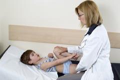 El quejarse lindo de Little Boy del dolor en su pierna al cuarto del doctor In The Consulting fotos de archivo