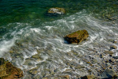 El quelpo y el musgo cubrieron los cantos rodados expuestos durante la bajamar como las ondas se lavan Fotos de archivo
