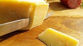 El queso cortó con un aperitivo del cuchillo que cocinaba en una tabla de madera tradicional, tiro a cámara lenta almacen de video