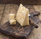 El queso de Holanda con los agujeros en un viejo tablero de madera y el queso amasan Foto de la vendimia lechería Espacio libre p fotografía de archivo libre de regalías