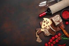 El queso de Maasdam cortó en una tabla de cortar con los tomates de cereza, el pan negro, el ajo y el romero, botella de vino, co imagen de archivo libre de regalías