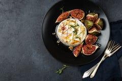 El queso del camembert coció con los higos, las nueces y la miel Imagen de archivo