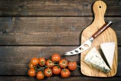 El queso, el cuchillo y los tomates están mintiendo en el escritorio Fotografía de archivo