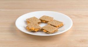 El queso llenó las galletas en una vista lateral de la placa blanca Fotos de archivo libres de regalías