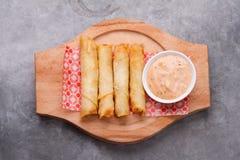 El queso rueda la placa con la salsa de cóctel servida en una placa de madera en los vagos rústicos fotografía de archivo