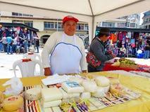 El queso sonriente de la mujer vende en el mercado abierto imagen de archivo