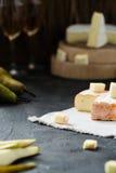 El queso suave francés de la región y del brie de Bretaña cortó, con la pera, los vidrios de vino blanco Fotografía de archivo