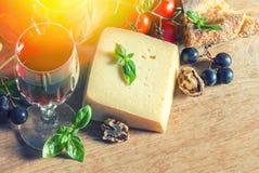 El queso, vino rojo, nueces, tomates, albahaca sale de las uvas Fotos de archivo libres de regalías