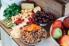 El queso y las frutas en un vintage adornaron maravillosamente la tabla Imagen de archivo