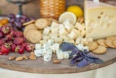 El queso y las frutas en un vintage adornaron maravillosamente la tabla Imagen de archivo libre de regalías