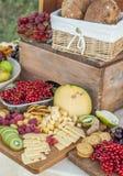 El queso y las frutas en un vintage adornaron maravillosamente la tabla Foto de archivo libre de regalías