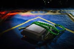 El Quran santo con las gotas en una estera de rezo, musulmanes Tasbih es una cadena de gotas de rezo junto con la cual es utiliza Foto de archivo