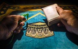 El Quran santo con las gotas en una estera de rezo, musulmanes Tasbih es una cadena de gotas de rezo junto con la cual es utiliza Imagenes de archivo