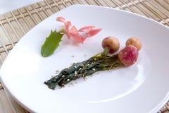 El rábano Kimchi y una flor adornan. Fotografía de archivo