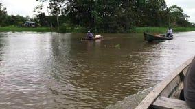 El río Amazonas en Colombia - una canoa del motor con los pasos masculinos del conductor cerca almacen de metraje de vídeo