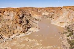 El río anaranjado como viaja abajo del barranco río abajo desde el Augrabies cae Imagenes de archivo