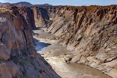 El río anaranjado como viaja abajo del barranco río abajo desde el Augrabies cae Imagen de archivo
