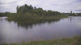 El río ancho tranquilo con la plataforma de madera es rodeado por el bosque y el pueblo almacen de metraje de vídeo
