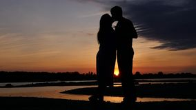 El río con una puesta del sol dibujan a una chica joven y a un individuo el uno al otro al beso en un lugar romántico HD, 1920x10 almacen de video