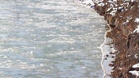 El río congelado del hielo está derritiendo en primavera con fluir de las escamas del hielo Hielo agrietado que flota en el río e almacen de video