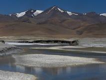 El río de la montaña, el canal pasa a través de los suelos salinos, el agua azul refleja los picos de los altos picos, el cielo a Fotografía de archivo libre de regalías