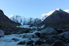 El río de la montaña fluye de los picos nevosos Fotos de archivo libres de regalías