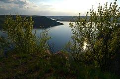 El río enorme Dniéster fluye entre las altas colinas escarpadas cubiertas con la hierba verde enorme de la primavera contra el ci imágenes de archivo libres de regalías