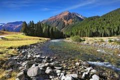 El río entre prados verdes de la montaña Foto de archivo