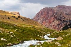 El río fluye abajo de la colina de la hierba con la montaña del colorfull en fondo Fotos de archivo