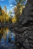 El río fluye entre las rocas y el bosque del taiga Imagen de archivo