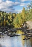 El río fluye entre las rocas y el bosque del taiga Foto de archivo