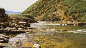El río rápido de la montaña atraviesa un valle de la montaña en las montañas del Cáucaso almacen de metraje de vídeo