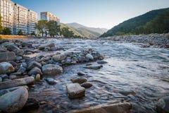 El río rápido de la montaña fluye en las cercanías de la ciudad cerca de los edificios altos foto de archivo libre de regalías
