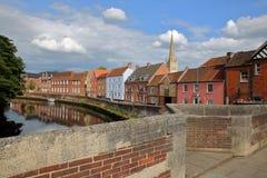 El río Wensum de la orilla en Norwich Norfolk, Reino Unido con las casas coloridas y la torre y chapitel de la catedral en el bac fotos de archivo