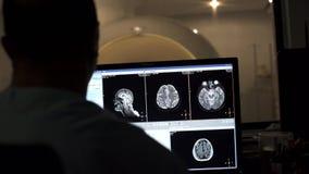 El radiólogo procesa imágenes después de explorar al paciente en sitio de la radiología almacen de video
