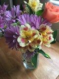 El ramo brillante de primavera florece en el florero de cristal Fotografía de archivo