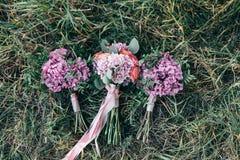 El ramo colorido de la boda hermosa tres para la novia y sus testigos miente en hierba Imagen de archivo libre de regalías