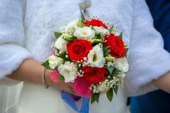 El ramo de la boda de flores blancas rojas se sostuvo por la novia Fotos de archivo libres de regalías