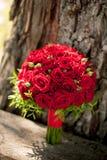 El ramo de la boda de rosas rojas est? en el fondo de la corteza de ?rbol foto de archivo libre de regalías