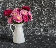 El ramo de otoño florece asteres en un jarro blanco fotos de archivo
