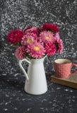 El ramo de otoño florece asteres en un jarro blanco, libro y una taza de té en un fondo oscuro Imagen de archivo