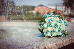 El ramo de rosas blancas con las cintas de la turquesa miente suavemente en la fuente Imagen de archivo libre de regalías