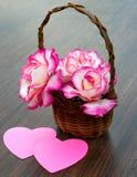El ramo de rosas está en una cesta de mimbre Imagen de archivo