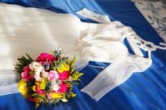 El ramo del vestido y de la boda de la novia miente en la cama Imagenes de archivo