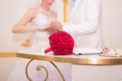 El ramo en la tabla al lado de la novia y del novio Foto de archivo libre de regalías