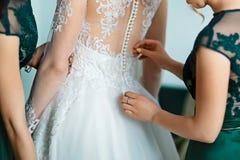 El ramo hermoso de la boda con las flores blancas y el verde se va en las manos de la novia y del novio en un vestido con un cord Imagenes de archivo