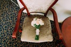 El ramo hermoso de la boda miente en silla del beige del vintage El ramo consiste en rosas rosadas y blancas Imágenes de archivo libres de regalías