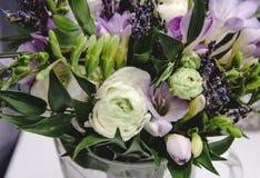 El ramo hermoso de la primavera de boda florece el ranúnculo del ranúnculo, fresia, lavanda en florero con la cinta violeta paste Fotos de archivo libres de regalías