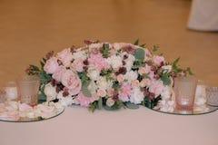 El ramo maravillosamente adornado de rosas adentro compone con las velas Fotos de archivo libres de regalías